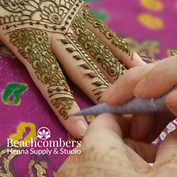 applying henna traditionally using a hand rolled henna cone with custom henna mix